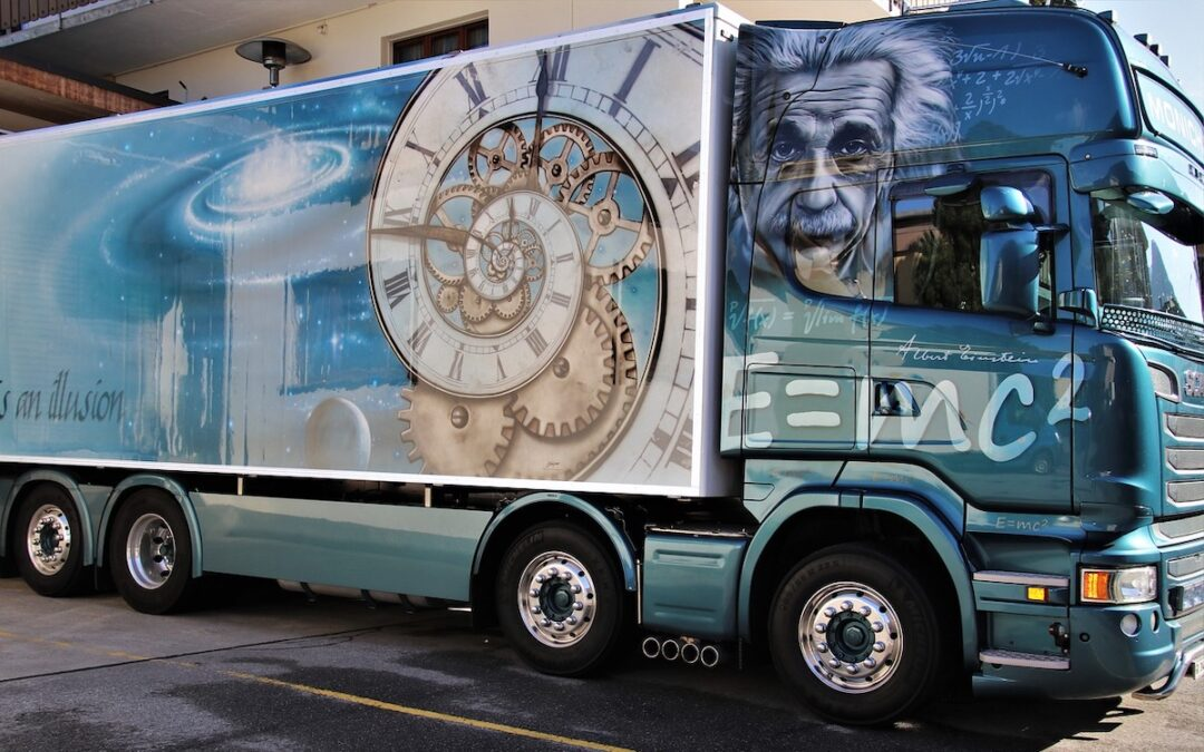 A 18-wheeler transport truck with an Einstein-theme mural painted on the side.