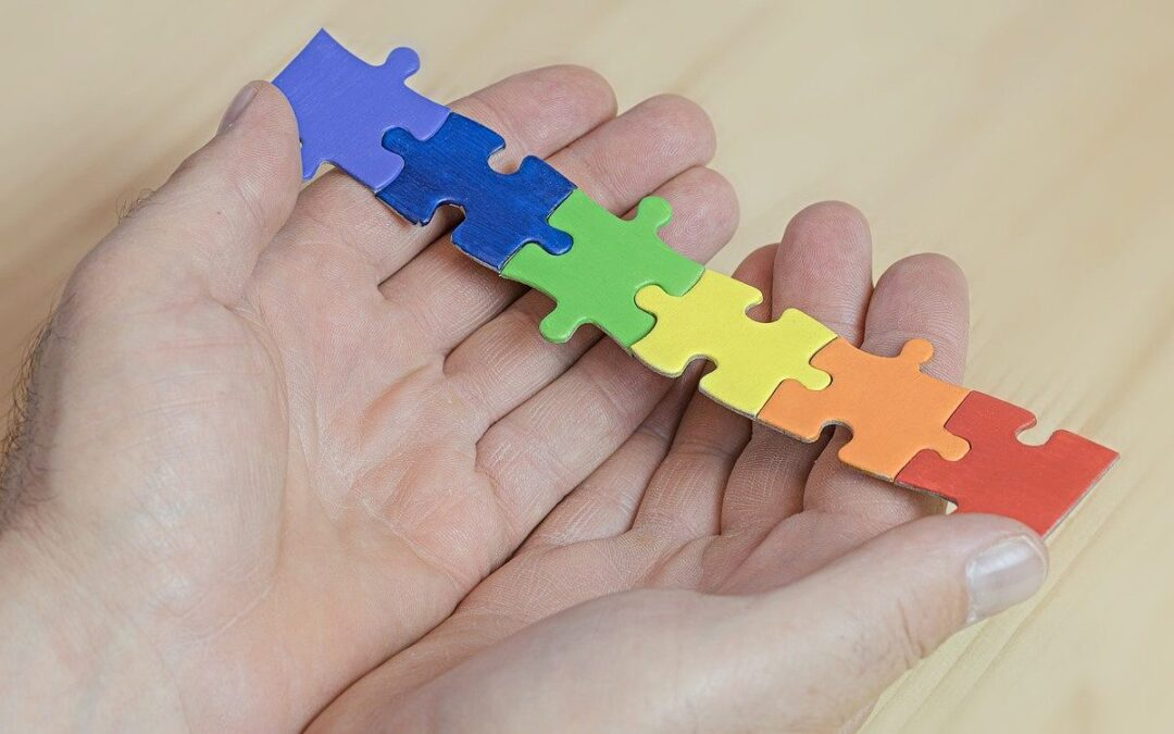 Hands holding connected multicolored jigsaw puzzle pieces