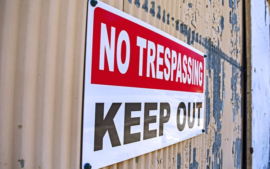 "A red, white and black ""no trespassing / keep out"" sign on a beige shipping container."