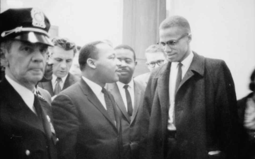 A black and white image of Malcolm X and Martin Luther King Jr before a press conference in 1964.