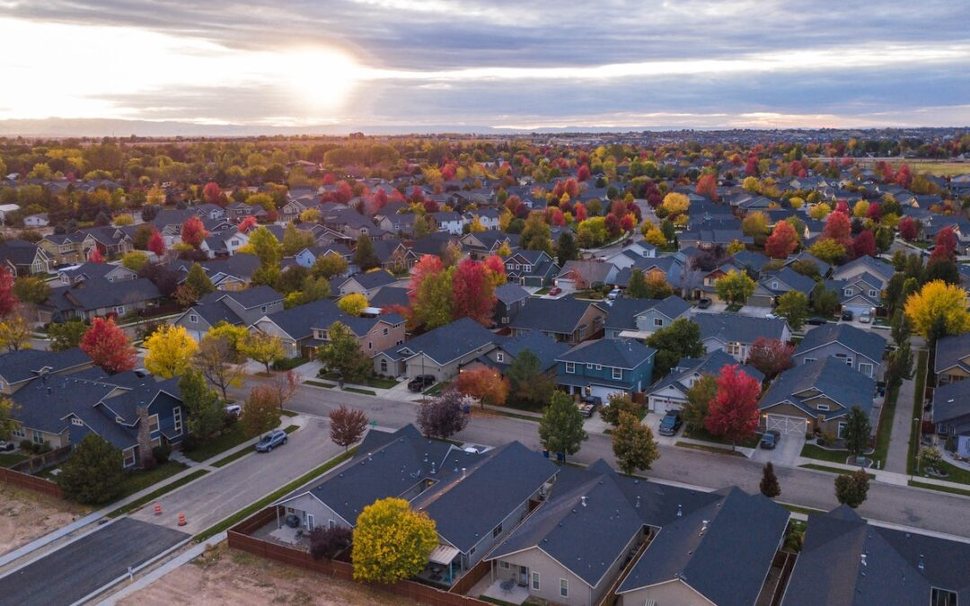 A suburban neighborhood as seen from above with trees showing fall colors.
