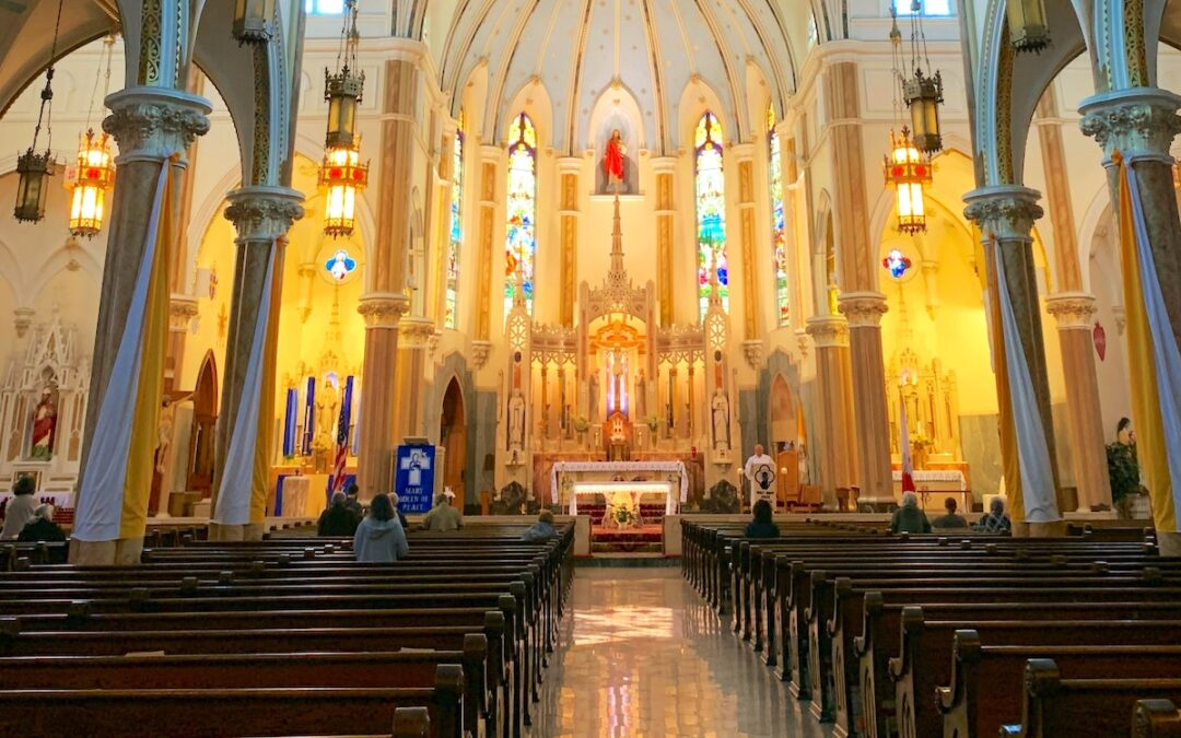 A worship space in a Catholic church with a few people toward the front and a lot of empty pews.