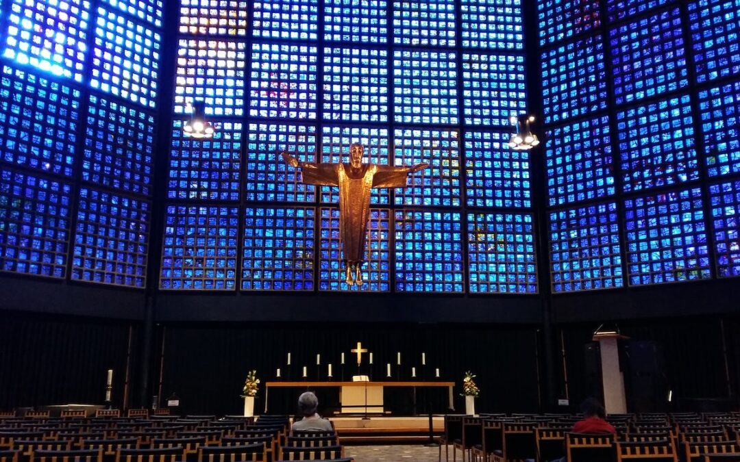 A church sanctuary with a Jesus icon suspended in the air and a few people sitting in the pews.