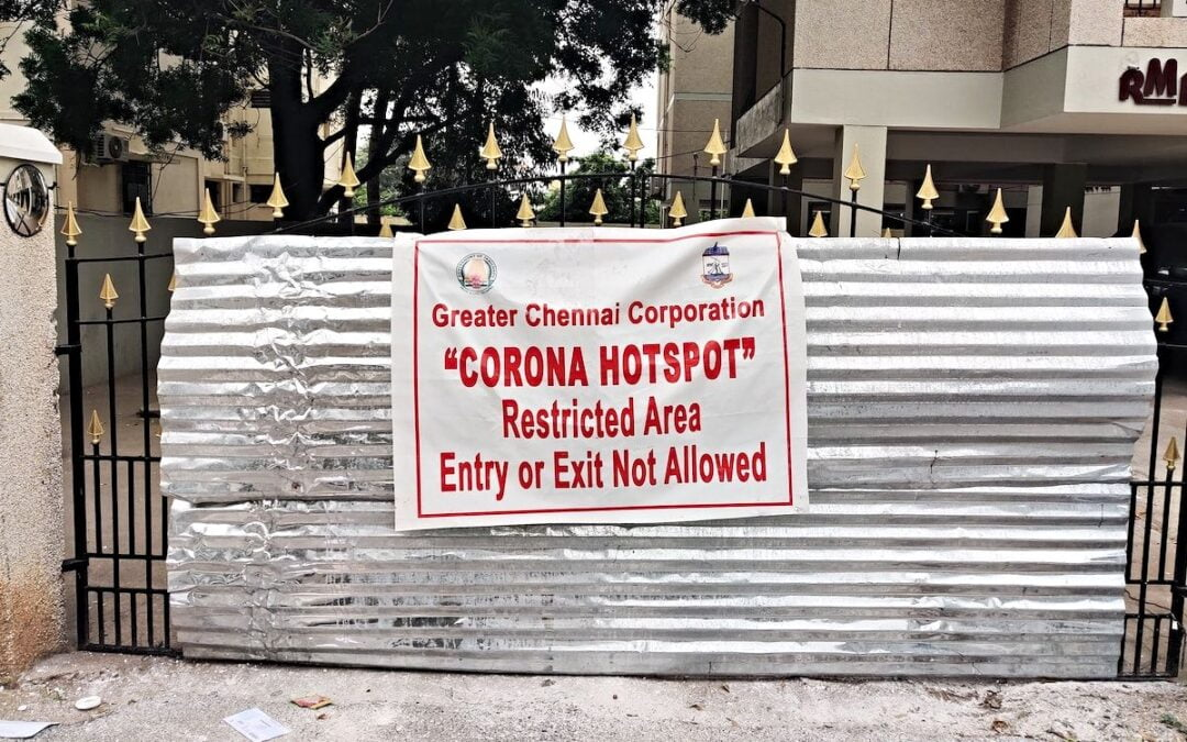 A COVID-19 hotspot warning sign posted on a metal fence in Chennai, India.