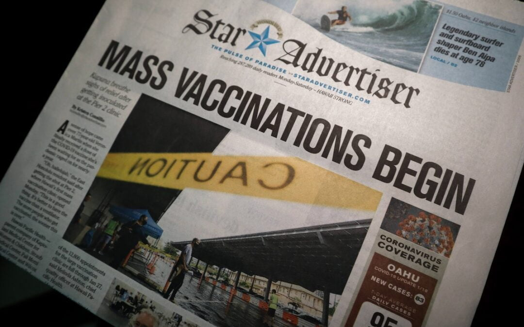 """A newspaper with the featured headline reading, """"Mass Vaccinations Begin."""""""