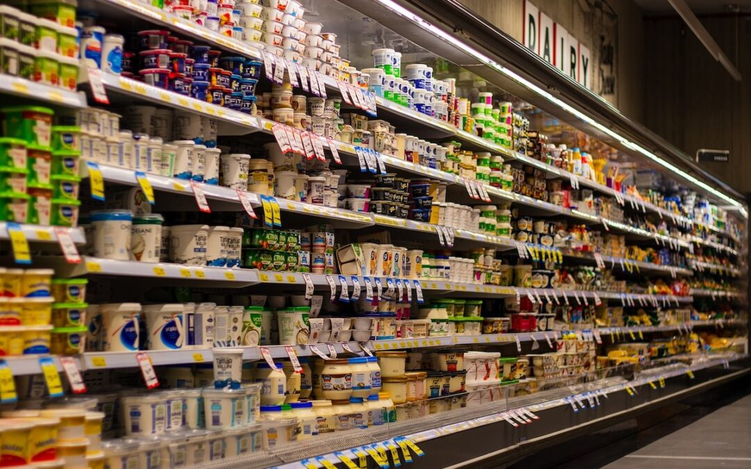 An aisle of refrigerated goods in a grocery store.