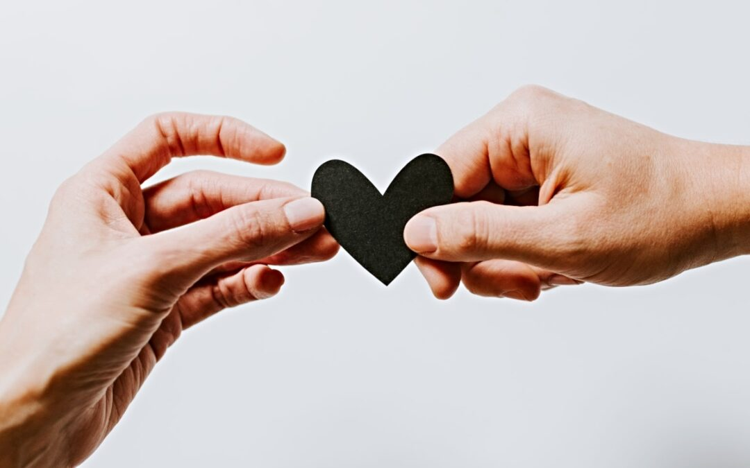 One hand giving heart silhouette to another hand
