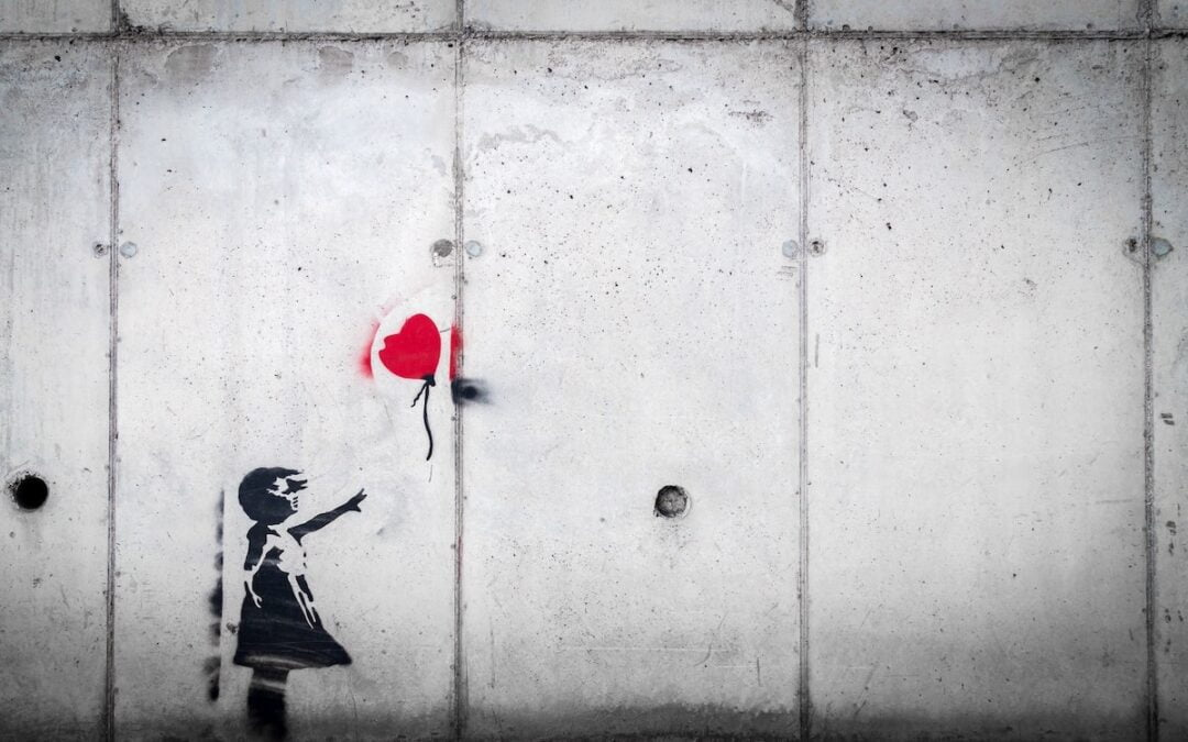 A wall painting of a young girl reaching out for a red balloon that is floating away.
