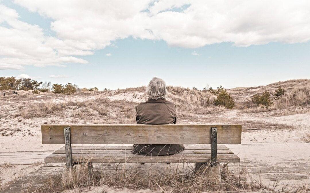 Elderly woman sitting on outdoor bench