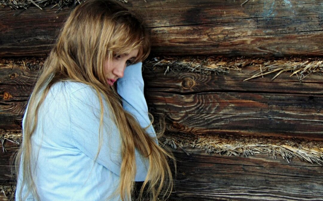 A woman in a blue shirt standing against a wooden wall.