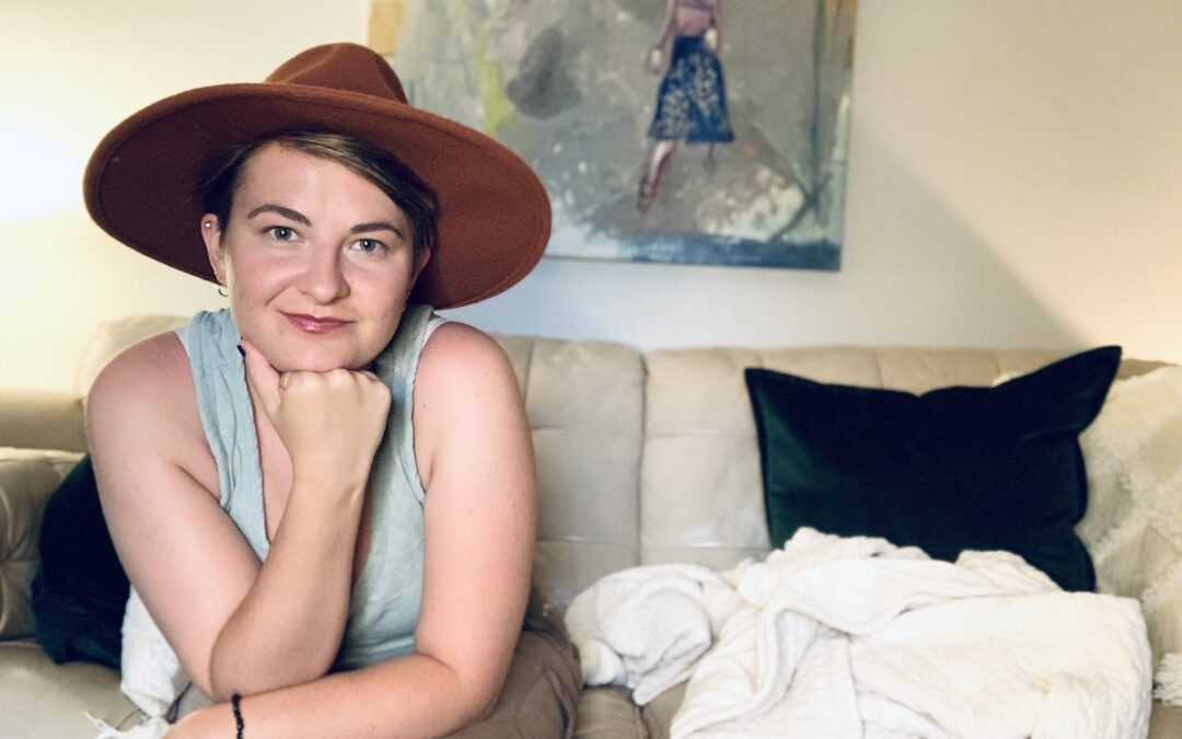 A woman in a red hat sitting on a couch.