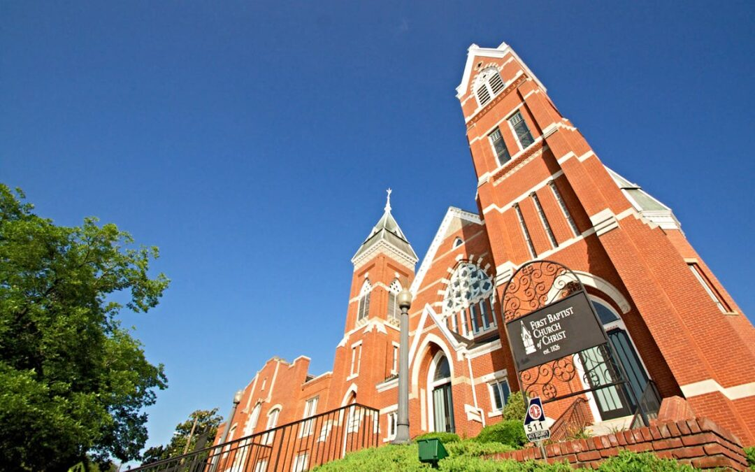 The exterior of a red brick church sanctuary.