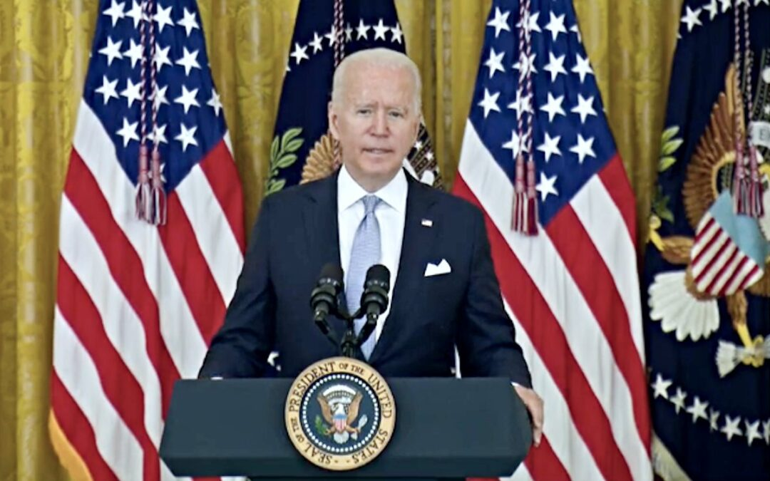 President Joe Biden standing behind a podium speaking with U.S. flags in the background.