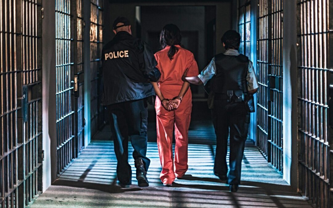 Prisoner in orange jumpsuit escorted by two police officers