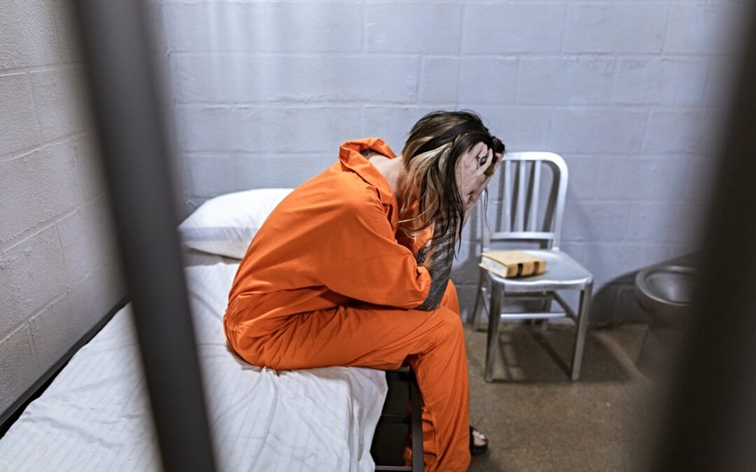 Woman prisoner seated in her cell