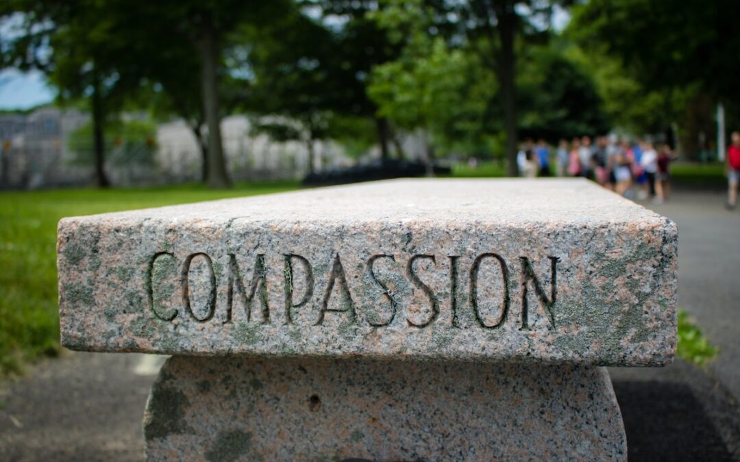 """A pink granite bench with the word """"compassion"""" etched into the side."""