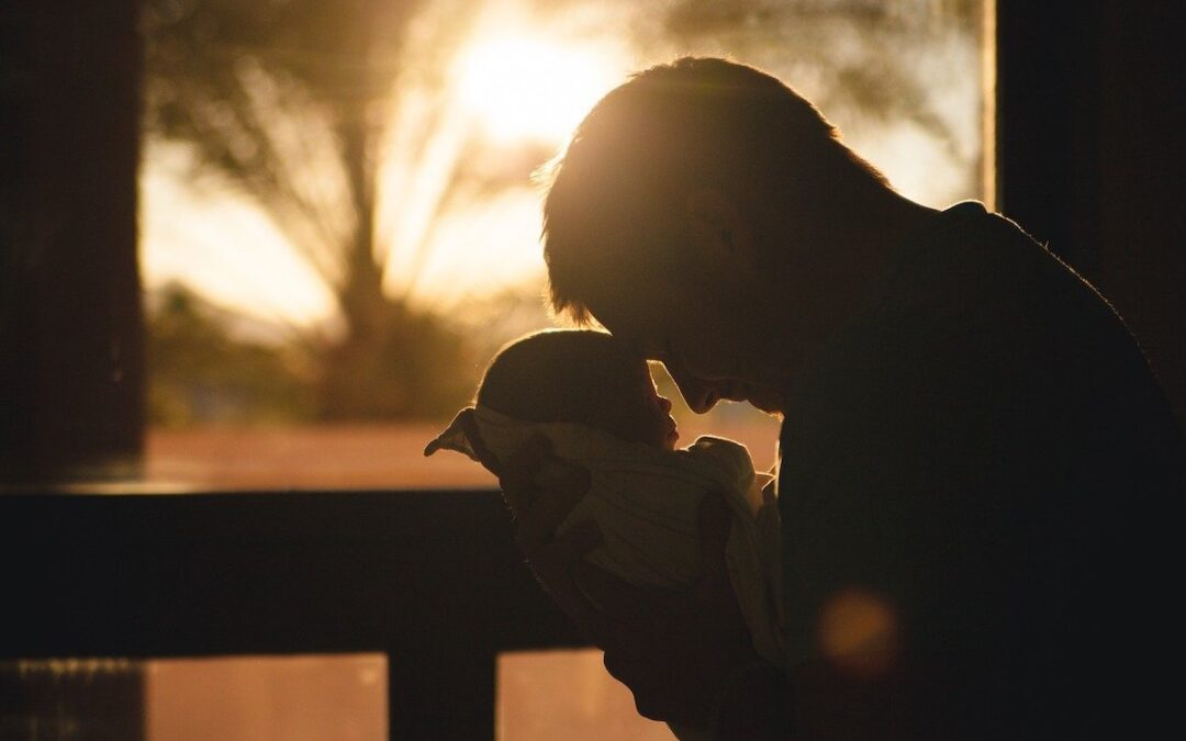 Silhouette of a father holding his young child