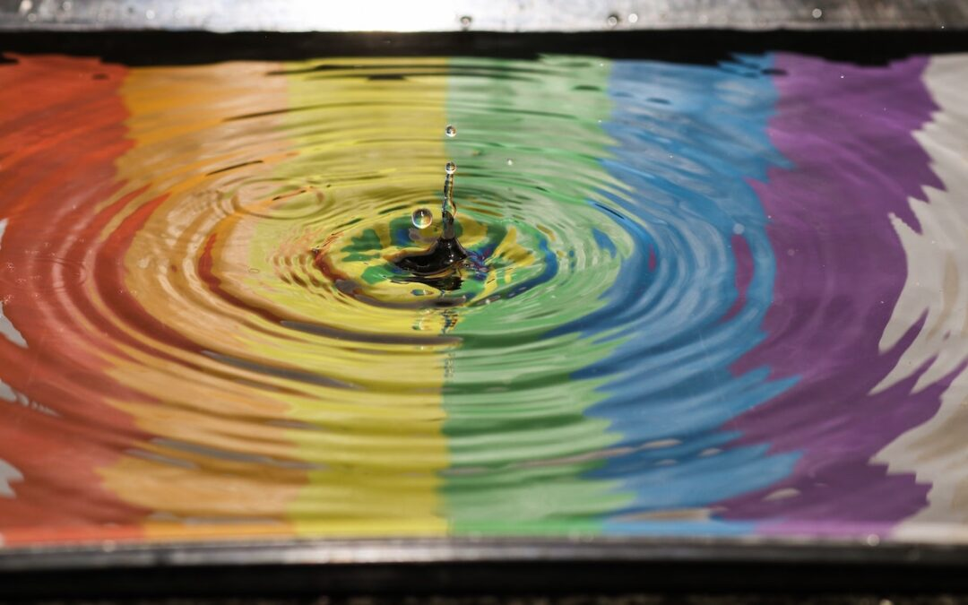 A rainbow reflected in water with ripples resulting from a splash in the middle.