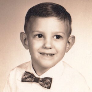 A young boy wearing a bowtie and white shirt.
