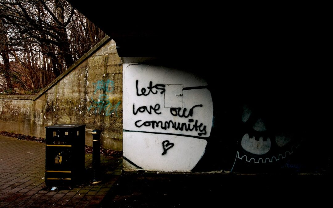 """The words, """"Let's Love Our Community"""" spray painted on a concrete wall."""