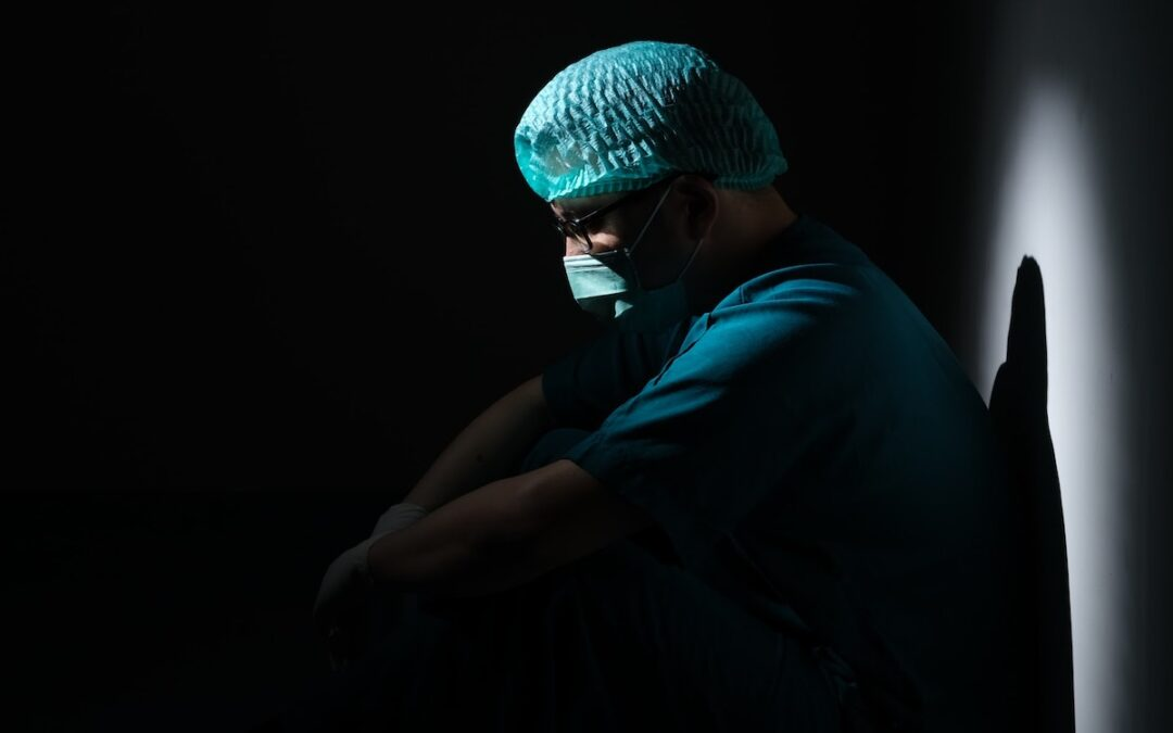 A medical worker sitting mostly in darkness with head bowed.