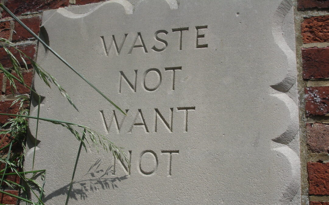 """A concrete marker on the side of a red brick building with """"Waste Not, Want Not"""" etched into it."""