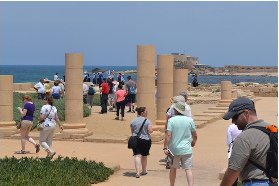 Tourists walking between columns with a sea in the background.
