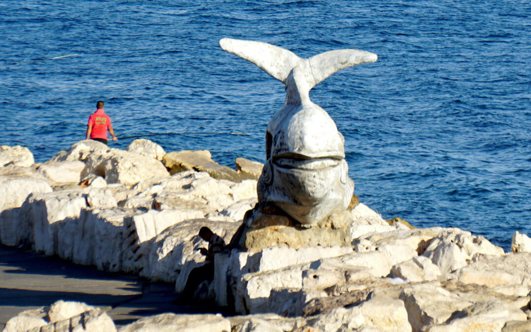 A whale statute amid rocks with water in the background.