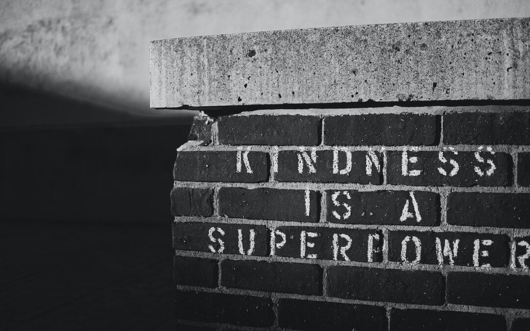 """A black-and-white image of a brick wall with the words, """"Kindness is a superpower"""" painted in block letters."""