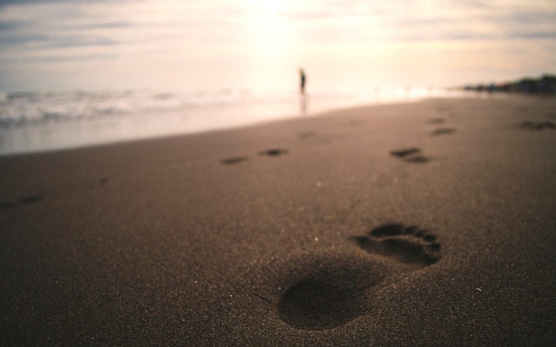 Footprints on a beach with the sun rising in the background.