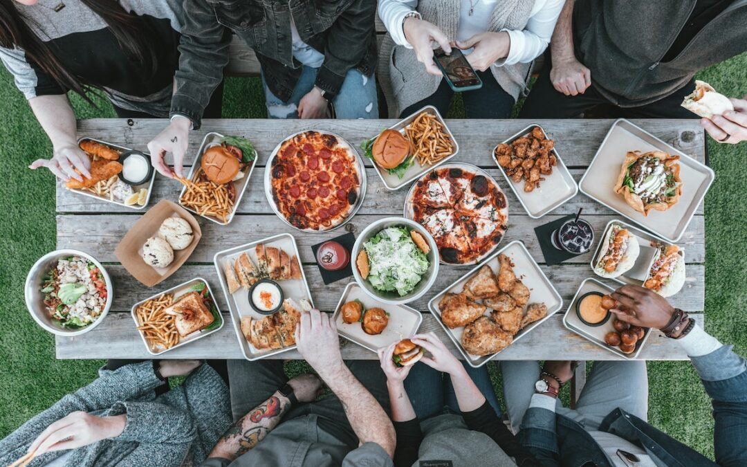 A table outside filled with plates of food and people reaching for items seen from above.