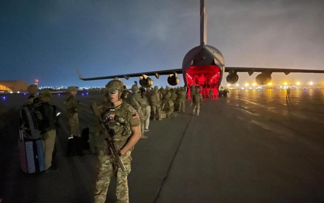 U.S. soldiers board a plane in Afghanistan at night.
