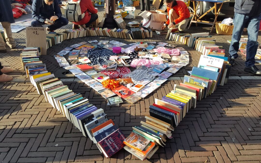 A book sale on the street with books arranged into a heart.