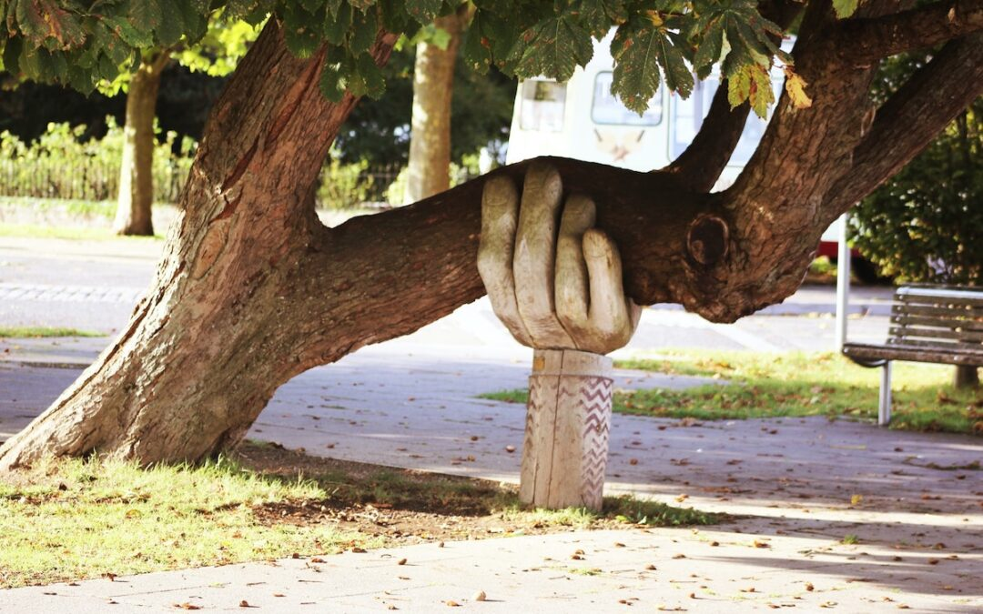 A wood-carved hand holding up a tree branch near a sidewalk.