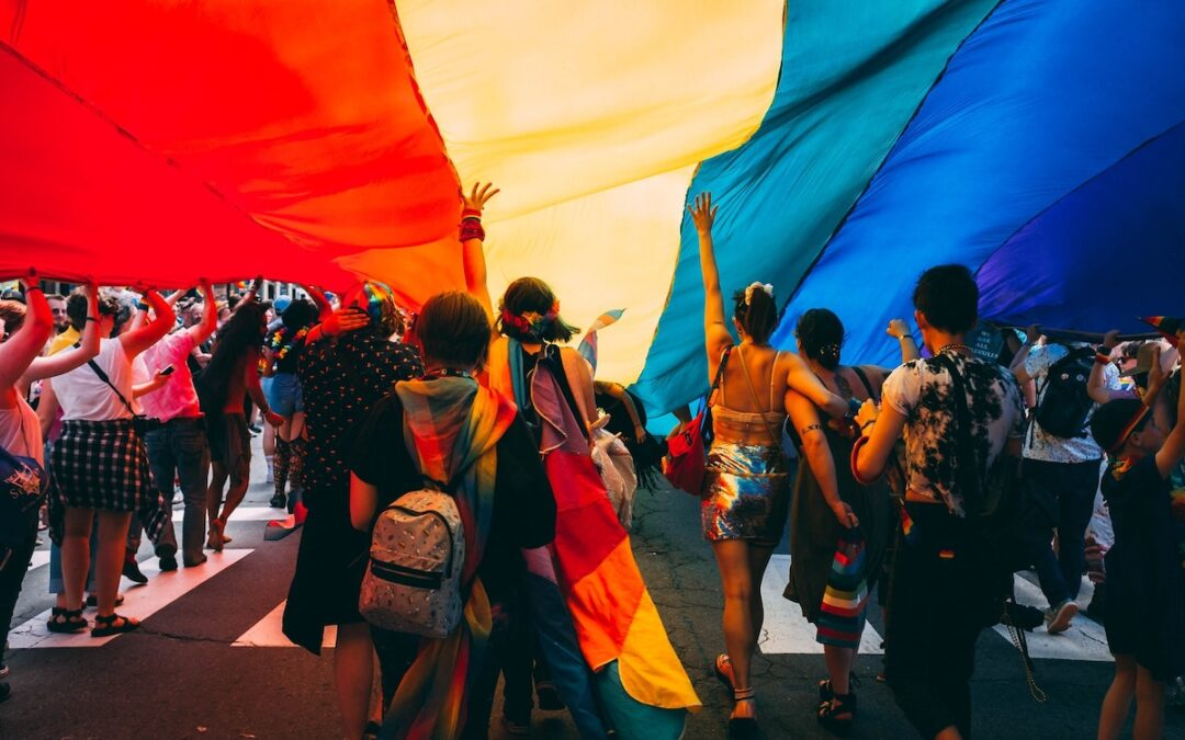 A rainbow flag in the air with several people standing underneath.